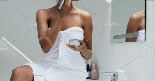 Beautiful young woman applying makeup on her face with makeup brush and looking into the mirror. Female getting ready in bathroom.