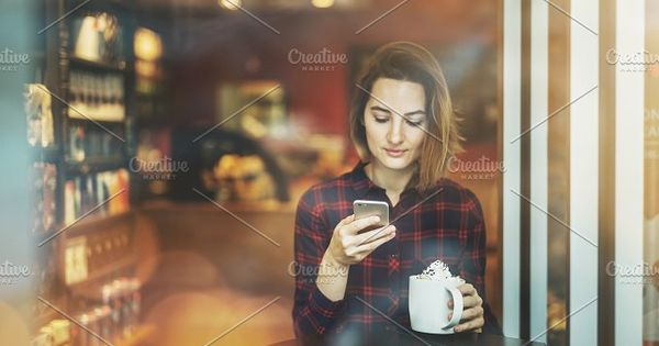 Charming smiling hipster girl chatting with her friends on smart phone and enjoying coffee