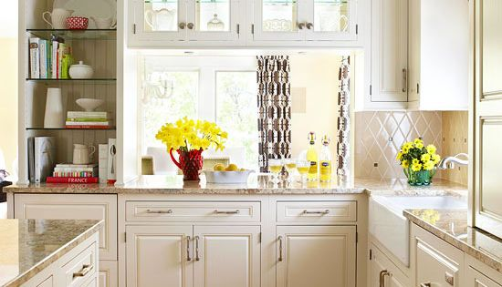 High ceilings, full length white cabinets, and double sided glass cabinets over