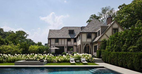 Pristine pool behind a modern tudor style home outdoor for Modern tudor house