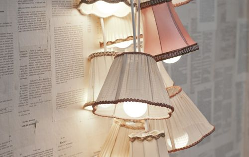Lamp Shade Chandelier, Old Book Pages Wallpapered on a Wall.