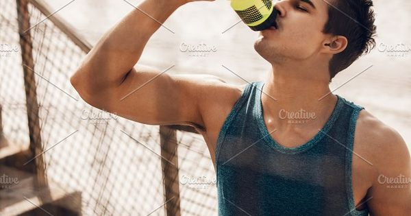Man drinking water after running workout at beach. Thirsty healthy male with fit body drinking water.