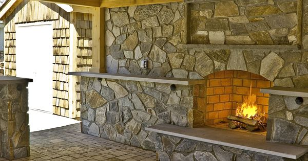 Outdoor fireplace custom masonry fireplace built into stone wall under a rustic timber pavilion - Bar built into wall ...