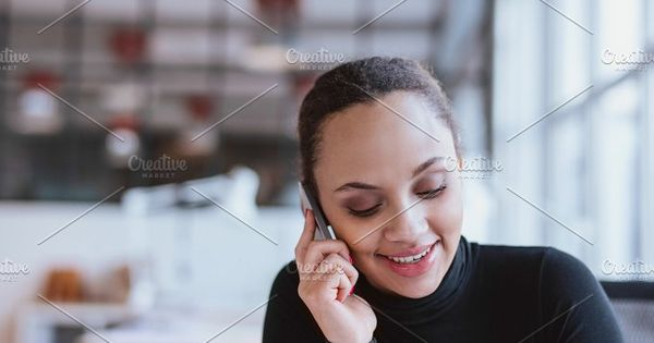 Closeup image of young woman talking on mobile phone. African american female model using cell phone at work.