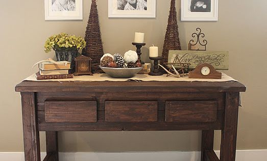 Love the sofa table AND hanging picture frames from a curtain rod!