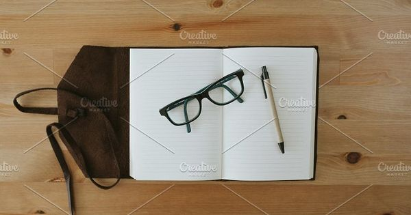 Journaling, notebook with pen and glasses on the wooden table