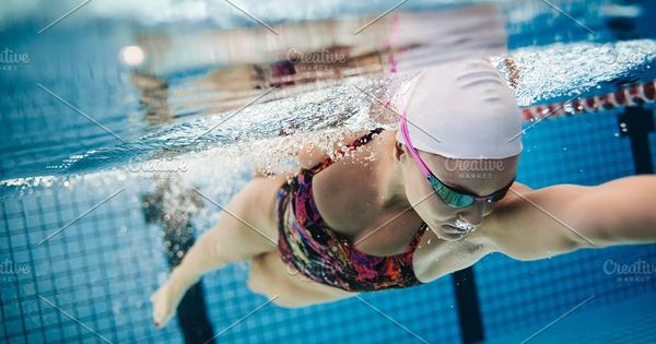 Underwater shot of young female swimmer swimming in pool. Fit young female swimmer training in the pool.