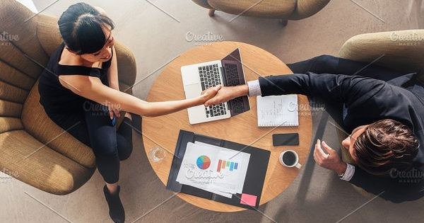 Top view of young business colleagues shaking hands on deal. Charts and laptop on table showing statistics and graphics.