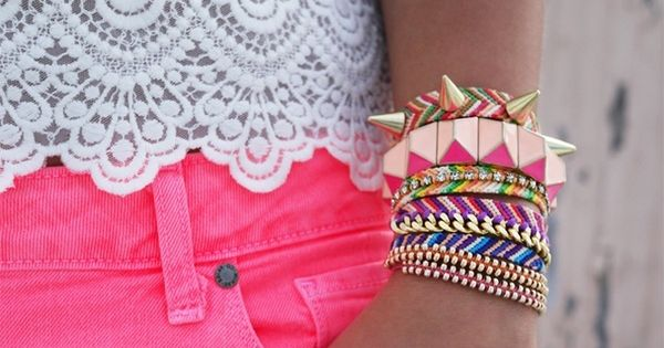 Neon pink jeans, lace top, stacked bracelets.