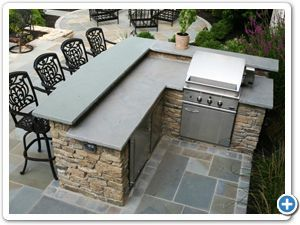 Outdoor Fieldstone Kitchen Featuring Raised Stone Bar Counter Grill Refrigerator And Trash Encloser Backyard Patio Backyard Kitchen Outdoor Kitchen Bars