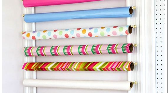 LOVE this gift wrap organizing idea! Mount cup hooks to a picture