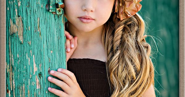 Beautiful young girl behind turquoise green weathered door with a variety of