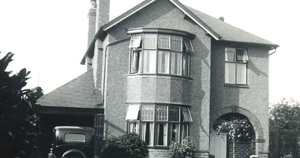 Detached assymetrical house with bay windows and arched for 1930s bay window construction