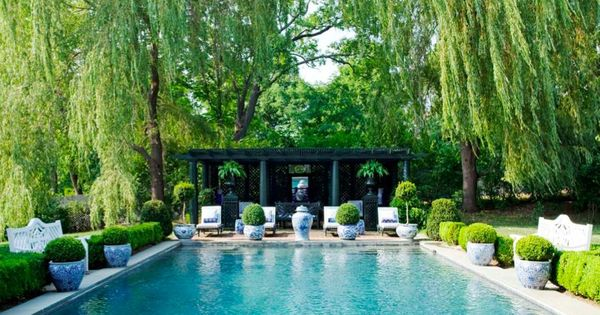 Blue and white planters around pool with weeping willows