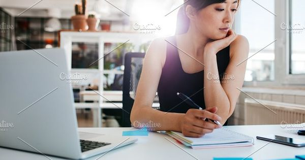 Shot of young asian woman working at her desk, writing notes. Businesswoman at her workplace.
