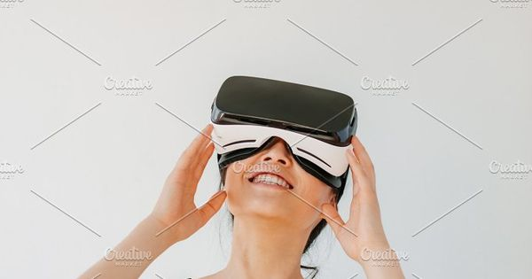 Vertical shot of young woman using the virtual reality headset against grey background. Happy female model wearing VR goggles.