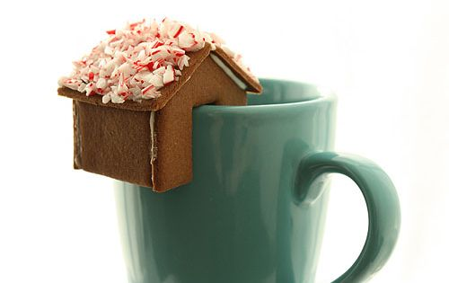 Gingerbread house perched on the edge of a mug of eggnog or