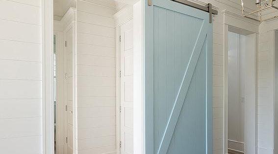 White Shiplap Walls Frame A Powder Blue Barn Door On A
