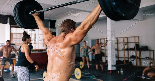 Rear view shot of muscular bodybuilder lifting weights in gym. Fitness male during cross training.