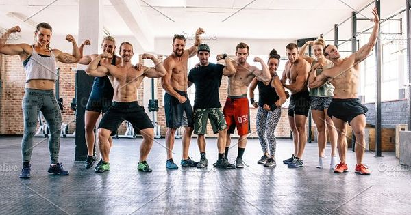 Large group of male and female bodybuilders showing muscles together in gym. Fitness class flexing muscles in health club.