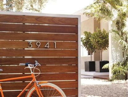 Modern house numbers on wooden privacy fence