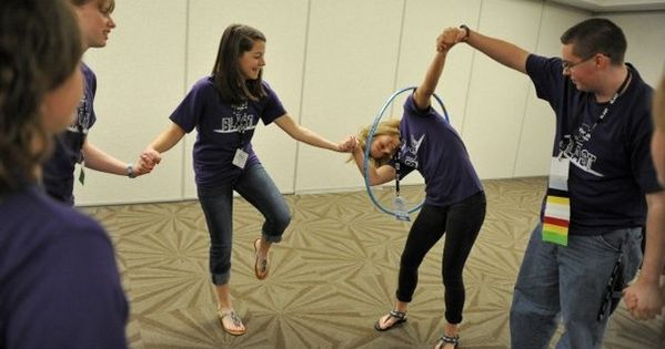 Students race to pass a hula hoop around each other while ...