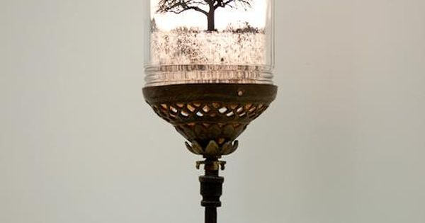 A photograph of a bare tree floats, illuminated inside a reclaimed glass