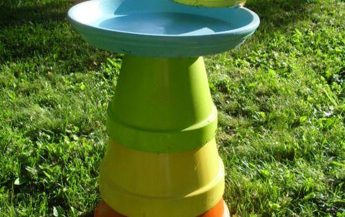 Brightly colored clay pots stacked to make a bird bath/ bird feeder.