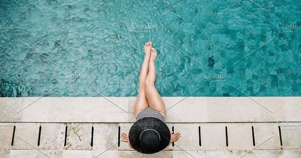 Young woman in hat relaxing near swimming pool