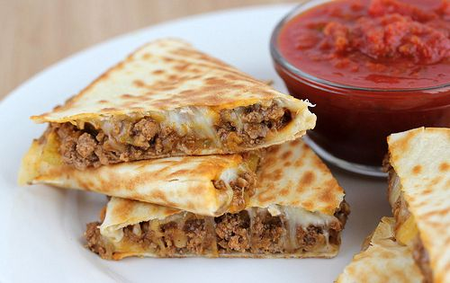 Beefy quesadillas! These quesadillas use a burrito-style filling which consists of taco seasoned ground beef, refried beans, and green chilies.  You can use whatever type of cheese you like but I prefer Mexican cheese blend. These quesadillas go great se...