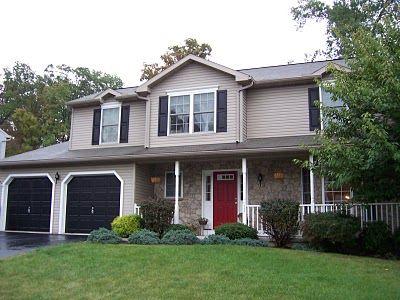 Red Door Grey House light grey house with dark grey shutters and dark grey garage door