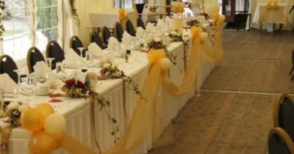 wedding reception bridal party banquet table with yellow tulle swags and balloons