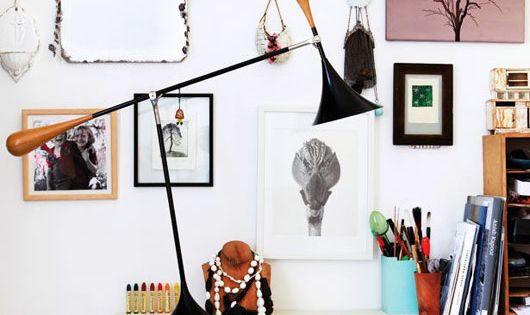 White office space. White desk. Lamp. Eclectic wall art display.