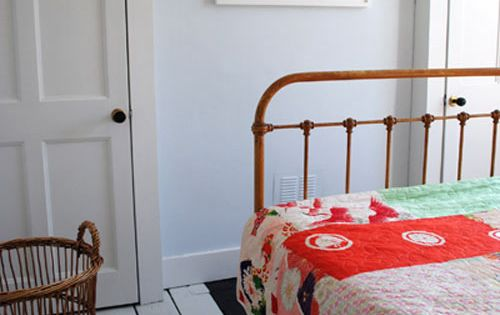 Wrought iron bed with white painted floors and patchwork quilt