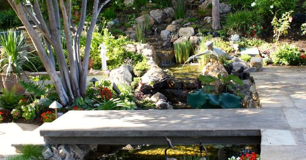 A narrow concrete bridge provides a path across a small for Ornamental garden ponds