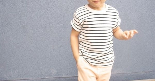 Hipster kiddo in a striped shirt, glasses and a bun.
