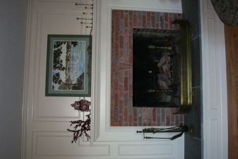 Dramatic fireplace makeover with wainscoting to cover the - Brick wall fireplace makeover ...