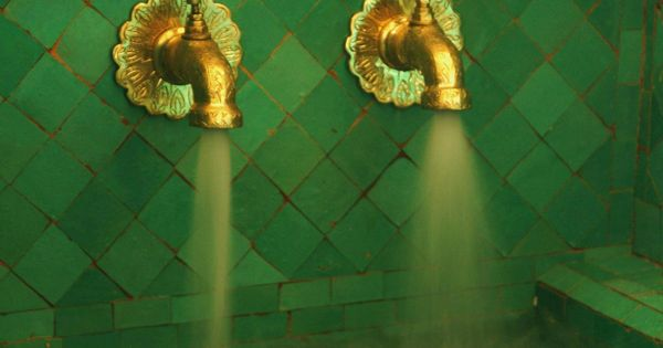 a turkish bath with green tiles and gold-colored brass taps. the color