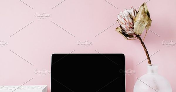 Pink styled workspace – Laptop with black screen on table with proteus flower and decoration.