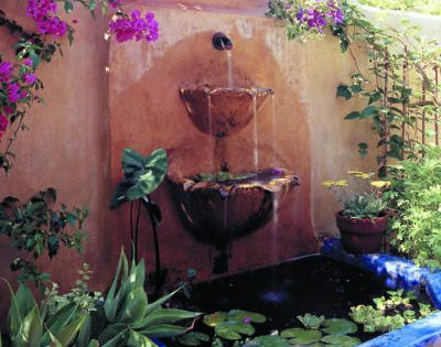 Against a rustic stucco wall, water trickles out of scalloped bowls into