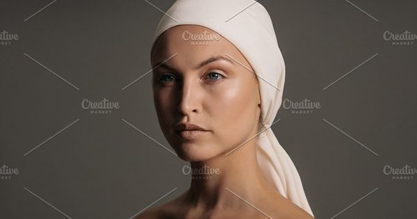 Close up portrait of young woman against grey background. Beautiful caucasian woman with a scarf wrapped on her head.