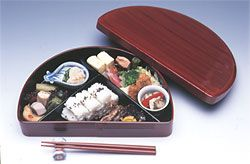 A hangetsu-type bento box, usually identified by its half-moon or semi-circular shape.  These boxes are also covered in lacquer for durability.