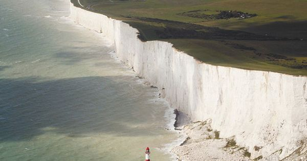 Beachy Head, England. White cliffs and a little candy striped lighthouse. travel,