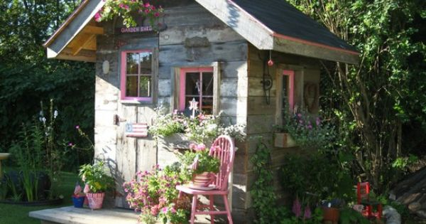rustic garden shed, pink accents ... flower bed surrounded w/ stones reminds