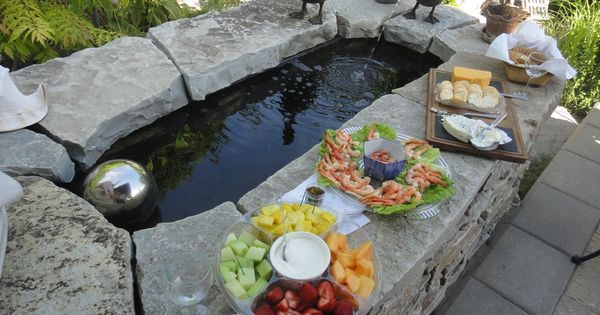 Koi pond from galvanized water trough and stone surround for Bathtub fish pond