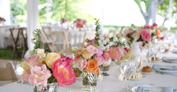 Simple table decoration: white table cloth, vases with flowers, a simple candles