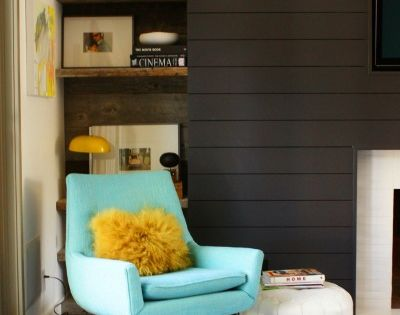 Turquoise chair makes a big impact against the dark walls