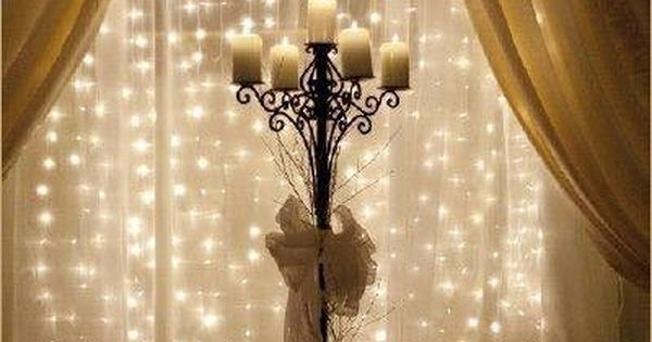 Strings of mini lights attached to curtain rod behind sheer fabric. Love