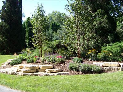 Natural Ledgerock Outcropping Stone Was Used To Create A Natural Retaining Wall To Support The F Stone Landscaping Landscaping Retaining Walls Landscape Design