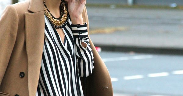 Camel coat on a black and white striped shirt with skinny jeans,